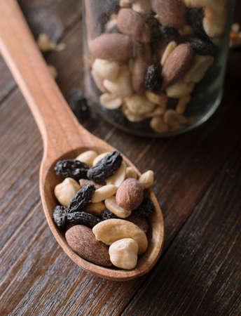 瓶がいっぱいのナッツとレーズンの木製の背景を持つスプーン。Cloae。 写真素材