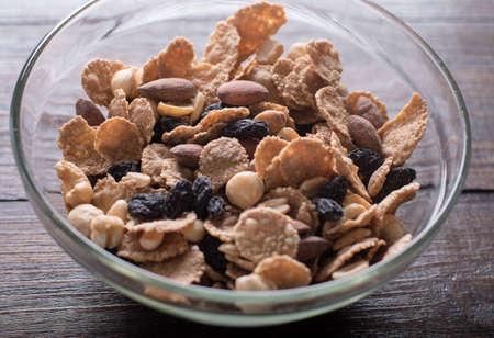 丼のオーツ麦フレーク ミックス ナッツと乾燥した木製の背景にフルーツ 写真素材