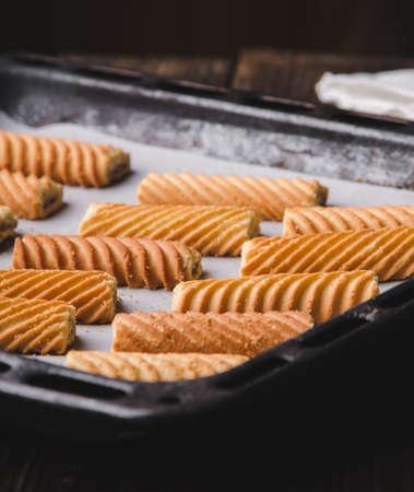 ベーキング シート上いくつかの自家製の甘いクッキー。オーブンで焼きます。 写真素材