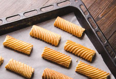 ベーキング ペーパーと素朴な木製のテーブルの手作りジンジャーブレッド クッキー。オーブンで焼きます。 写真素材