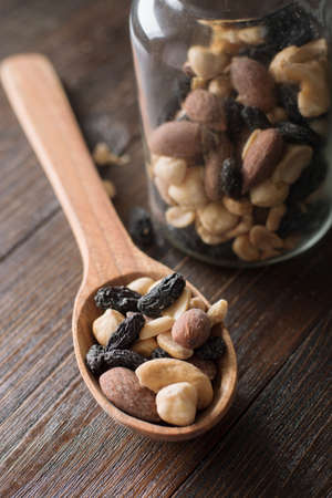 Spoon with jar full of nuts and raisins on a wooden background. Top view.