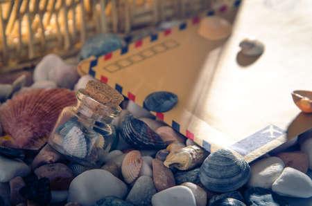黄色い封筒、ガラスの殻は暖かな光でマルチカラーの小石のビーチの jar します。
