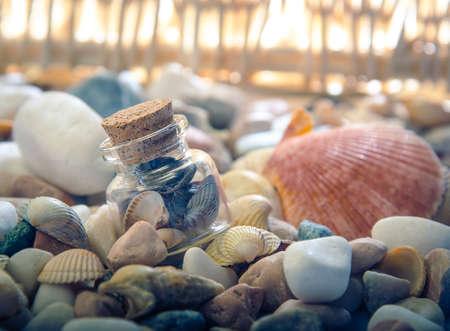 暖かな光と礫浜のガラスの瓶にシェル。正面から見た図。 写真素材