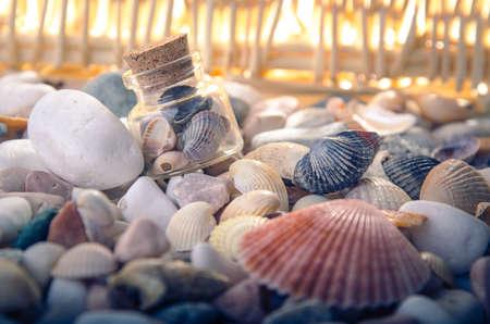 暖かな光と海の小石ポグロムにガラスの瓶にシェル。正面から見た図。