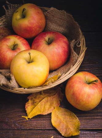 木製の背景にバスケットと秋にリンゴの葉します。