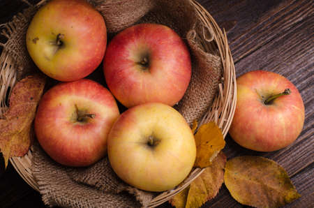 apples in the basket and autumn leaves on a wooden table.