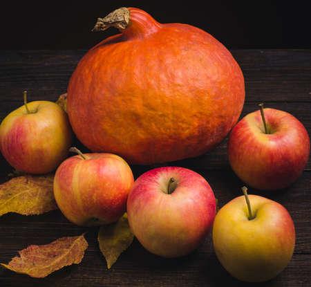 カボチャ、バスケットのリンゴ、木製の背景に秋の葉と静物。
