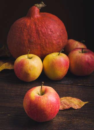 木製の背景にカボチャ、リンゴ、秋の葉。