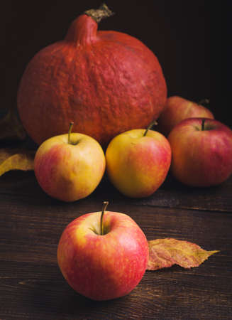Pumpkins, apples and autumn leaves at wooden background.