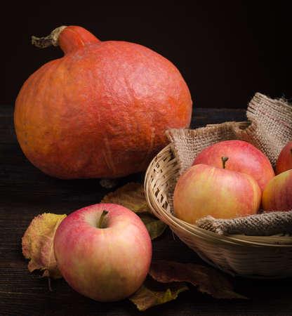 カボチャは、バスケットにりんごや木の背景に秋の葉。