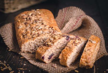 木製の背景に健康的なパンをスライス。種子を振りかけた自家製全粒フィットネスパン。
