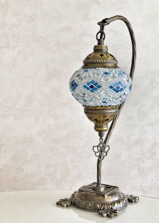 Mosaic glass lamp in oriental style on a gray background.