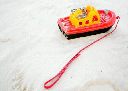 Childrens toy boat on the white sand. Foto de archivo