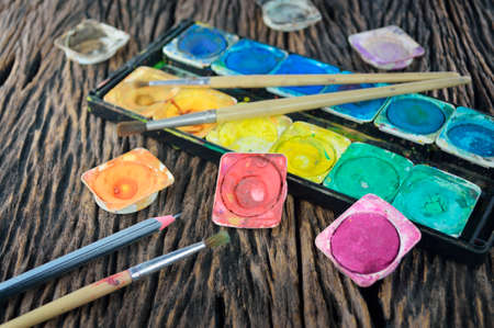 paintbox: Closeup of messy, used water color paint box and paint brush Stock Photo