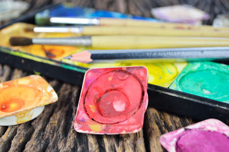 Closeup of messy, used water color paint box and paint brush photo