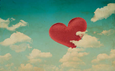 Fabric red heart on blue sky background, vintage style photo