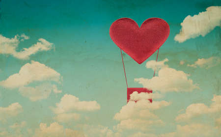 Fabric red heart air balloon on blue sky background, vintage style photo