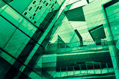 Glass of modern tower for business background, green tone photo