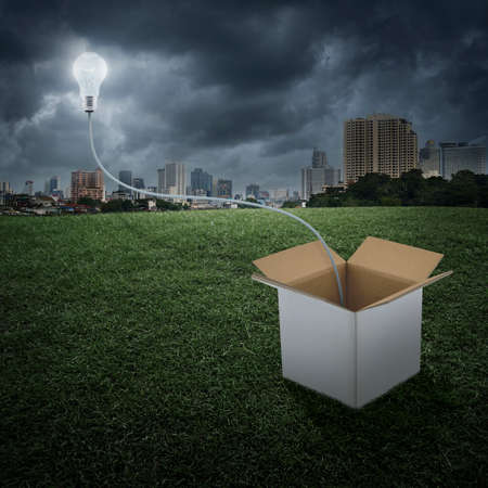 corrugated box: Glowing light bulb float over box on city background, Think outside the box concept Stock Photo