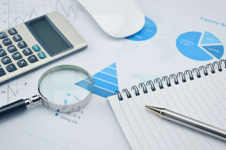 Book, magnifying glass, pen and calculator on financial chart and graph, accounting background