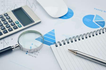 accounting: Libro, lupa, lápiz y calculadora en gráfico y gráfico financiero, experiencia en contabilidad Foto de archivo