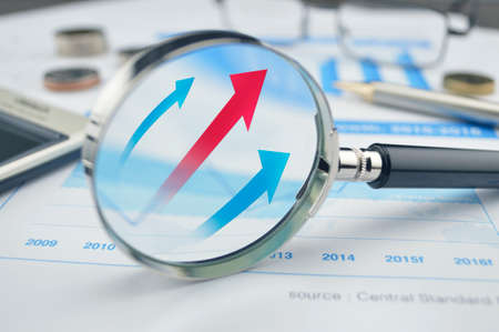 Rising red and blue arrow on magnifying glass, success concept photo