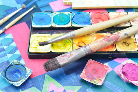 paint box: Closeup of messy, used water color paint box and paintbrush