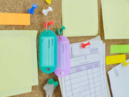 forgetful: tag name, colorful sticky notes, pin and key on cork board