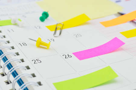 Colorful post It notes with pin and clip on business diary page
