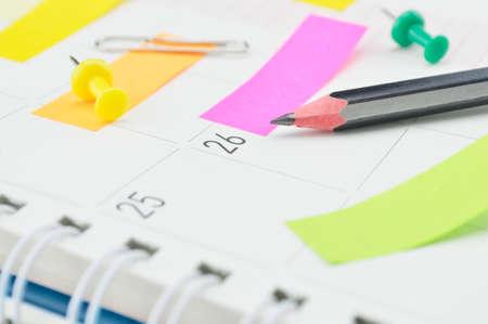 Potlood met kleurrijke post Het notitie en pin op bedrijfsdagboek pagina Stockfoto - 39099288