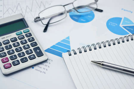 Pen book glasses and calculator on financial chart and graph, accounting background photo