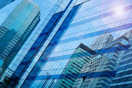 Reflect of modern city building on window glass tower blue tone Bangkok Thailand