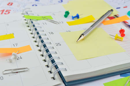 diary: Pencil with colorful notes and pin on business diary page Stock Photo