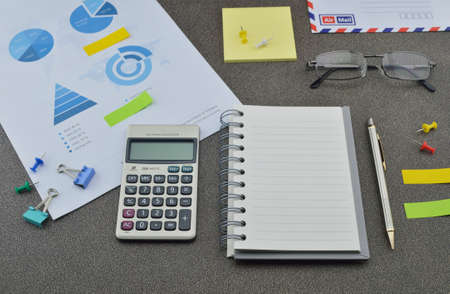 Pen book calculator glasses and financial chart and graph on table photo