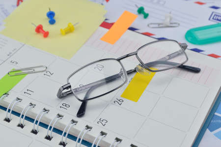 post it notes: Glasses with colorful post It notes and pin on business diary page Stock Photo