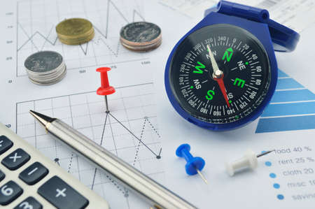 Red pin and blue compass on graph paper, target and win concept