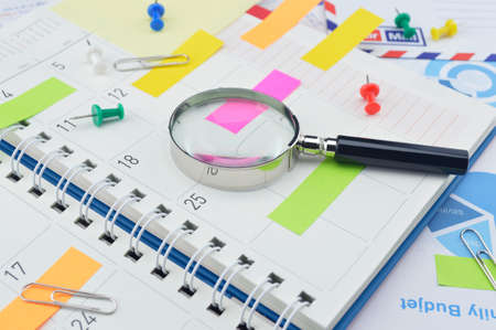 post it notes: Magnifying glass with colorful post It notes and pin on business diary page