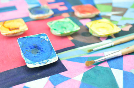 paintbox: Closeup of messy used water color paint box and paintbrush Stock Photo
