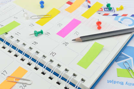 Pencil with colorful post It notes and pin on business diary page