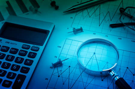 Magnifying glass, pin, pen and calculator on financial chart and graph, accounting background Stockfoto