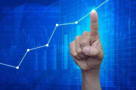 Hand point to graph on financial and business chart and graphs, success concept