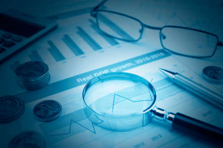 stock: Magnifying glass, glasses, calculator, pen, and coin on financial graph, accounting background Stock Photo