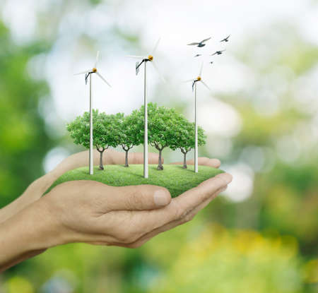 Wind turbines and trees on hands over green bokeh background, Ecological concept