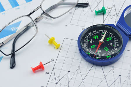 azimuth: Blue compass, pin and glasses on graph paper, success concept Stock Photo