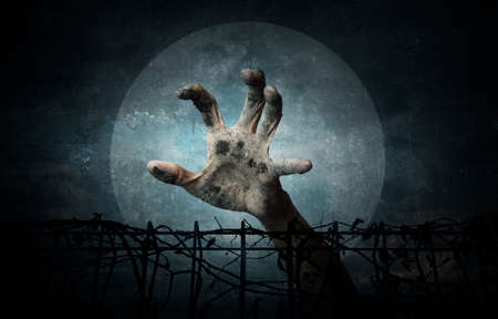 imprison: Hand over metal fence with dry leaves over dark sky and moon, grunge style, Halloween concept