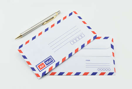 mail: Stack of air mail envelopes and pen on white background