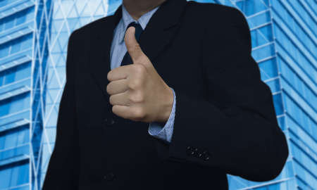 hand job: Businessman with thumbs up on city tower background