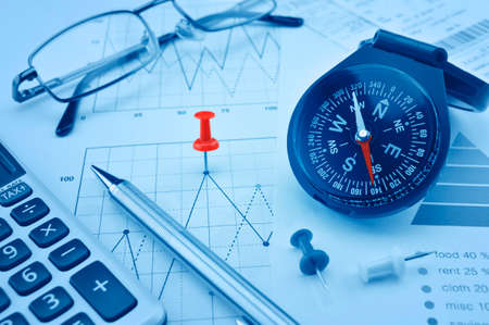 financial goals: Blue compass, pen and pin on graph paper, success concept Stock Photo