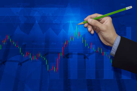 Businessman hand pointing pencil to stock market graph on city and graph background, Elements of this image furnished by NASA