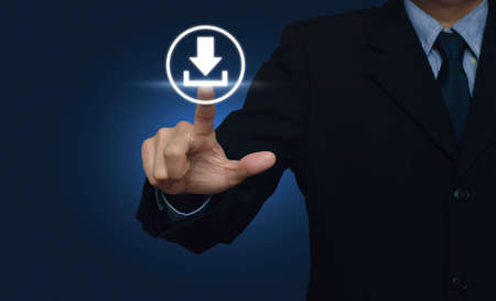 Businessman hand pushing button web download icon over blue background 스톡 콘텐츠